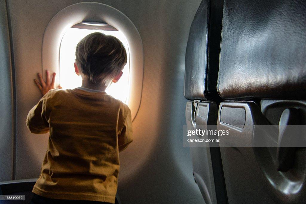 Toddler looking through an airplane window