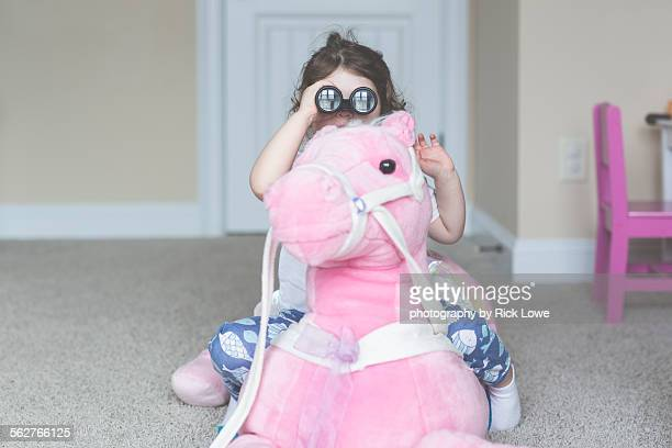 Toddler looking through binoculars riding a horse