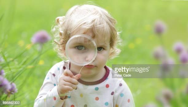 Toddler looking through magnifying glass in garden