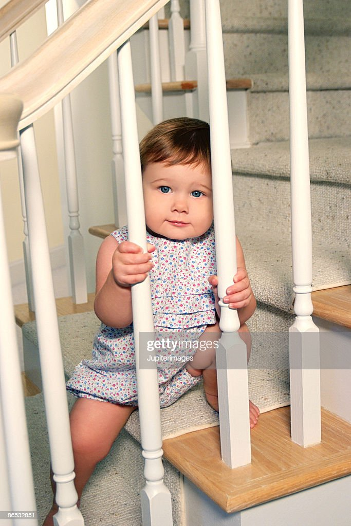 Toddler looking through staircase railing : Stock Photo