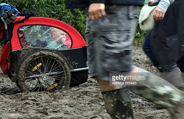 A toddler looks on from the comfort of a pushchair as they get pushed along a muddy path during the Glastonbury festival near Glastonbury Somerset on...
