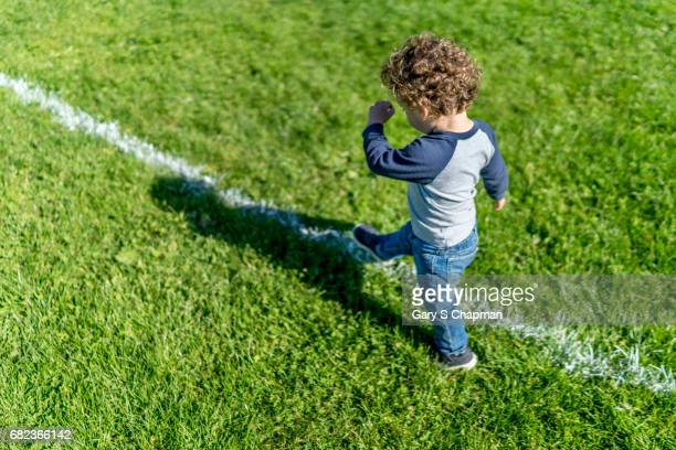Toddler marches on a school athletic field.