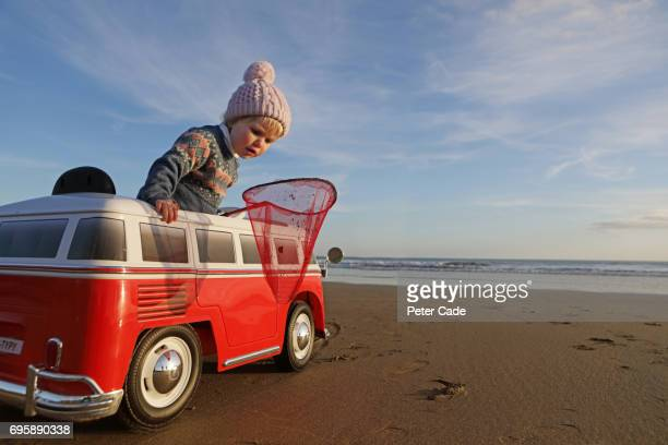 Toddler on beach in toy car with fishing net