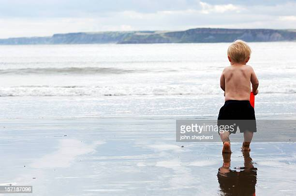 Toddler on beach running to the sea