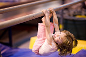 'Young girl, aged 2, proving it is never to early to start having fun and practicing good physical fitness. She is pulling herself up on uneven bars. Blue and yellow mats defocused in the background.
