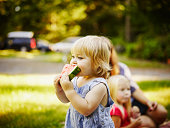Toddler outdoors biting into slice of watermelon