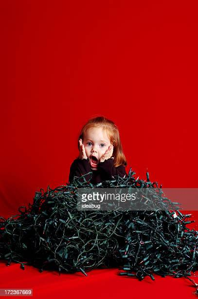 Toddler Overwhelmed by Pile of Tangled Christmas Lights