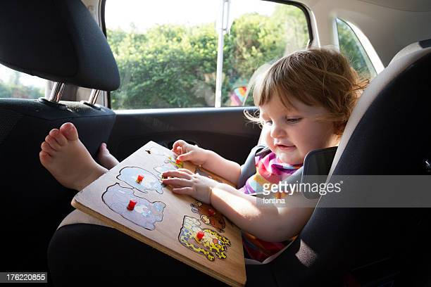 toddler playing in her car seat during the travel
