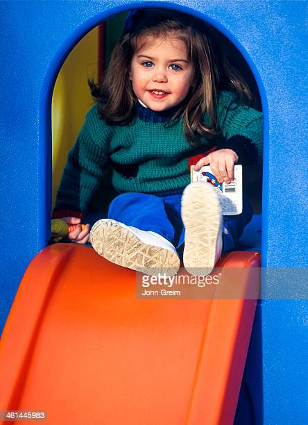 Toddler playing on playground sliding board