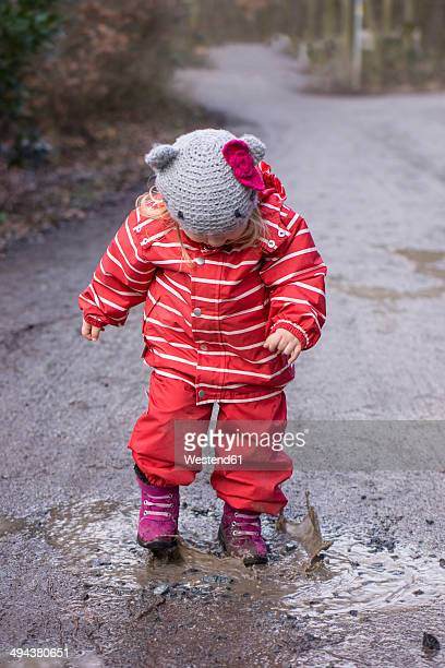 Toddler playing with a puddle of mud