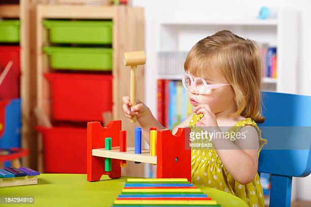 Toddler Playing With  Multi-coloured Toy In A Nursery