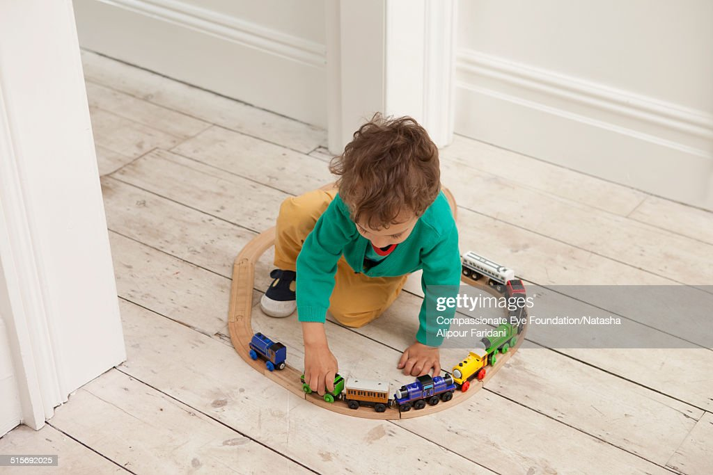 Toddler playing with toy train set