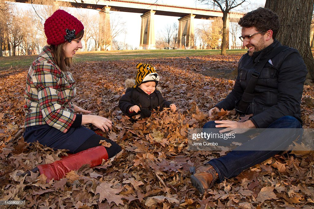 A toddler plays in fall leaves with his parents : Stock Photo