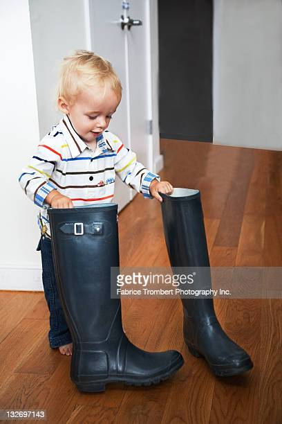 Toddler plays with adult boots