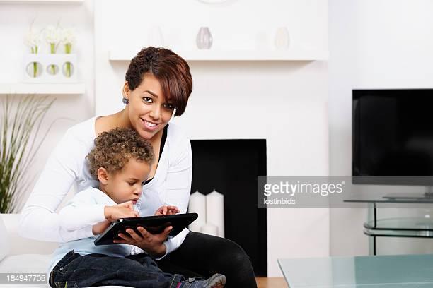 BÉBÉ/Enfant d'âge pré-scolaire et jeune maman et sœur à l'aide d'une tablette numérique