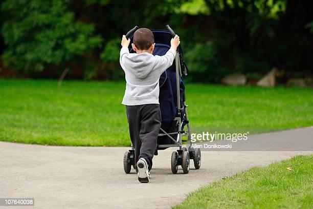 Toddler pushing stroller on park path
