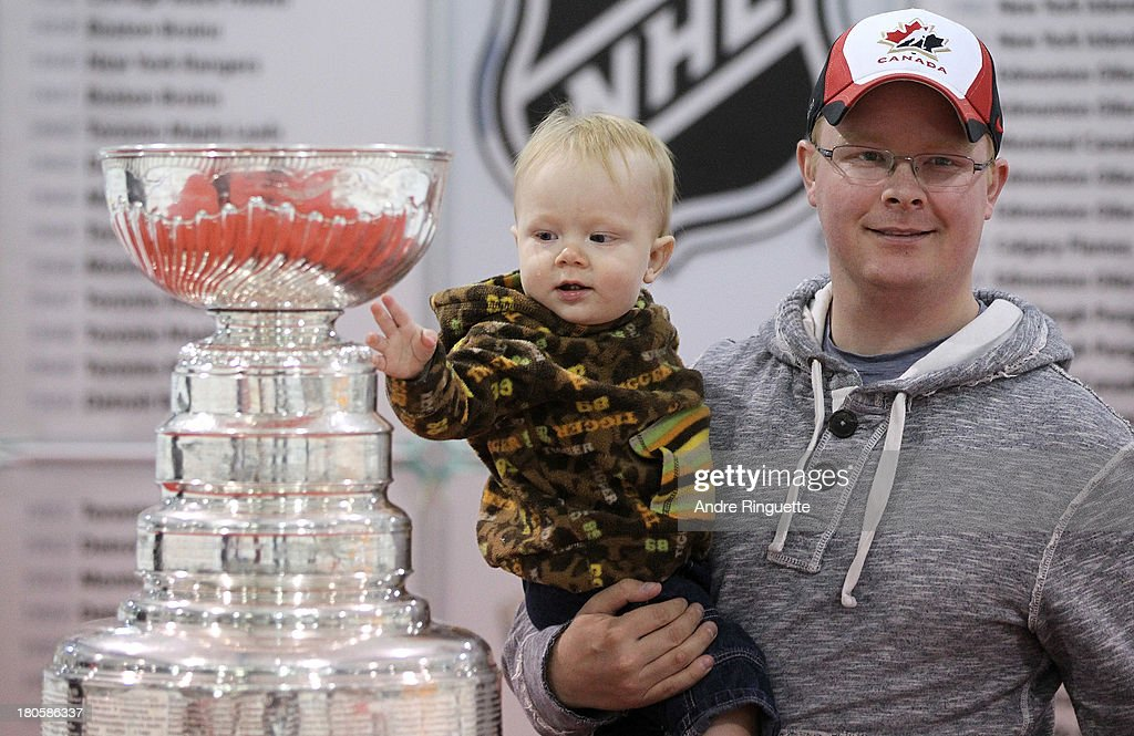 A toddler reaches out to touch the Stanley Cup as his father poses for a picture at the Stirling and District Recreation Centre during Kraft Hockeyville Day 2 on September 14, 2013 in Stirling, Ontario, Canada.