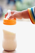 Toddler Reaching for Baby Bottle