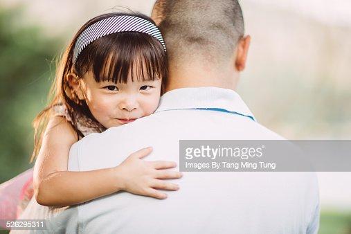 Toddler resting her chin on dad's shoulder in park