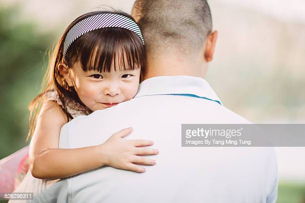 Toddler resting her chin on dad's shoulder in park