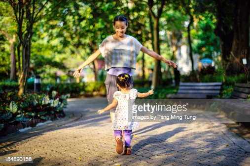 Toddler running to her mom in the park : Stock Photo