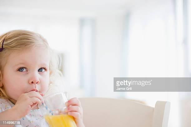 Toddler sipping orange juice through straw