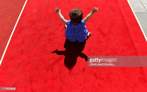 A toddler sits on a podium where normally guests of state listen to their national anthems when they are welcomed at the Chancellery in Berlin...