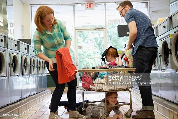 Toddler sitting in laundry basket, parents folding clothes, girl hiding under basket