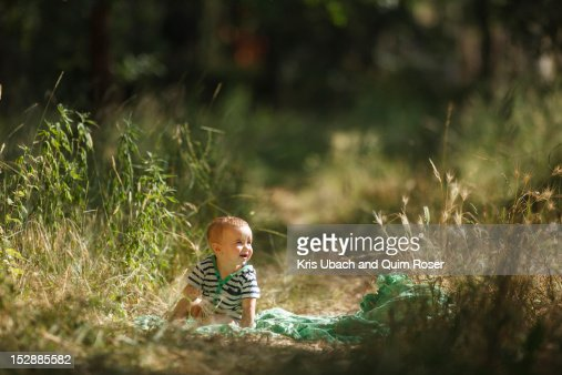 Toddler sitting on blanket in field : Stock Photo