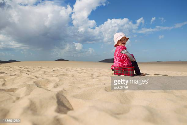 Toddler sitting on suitcase on beach