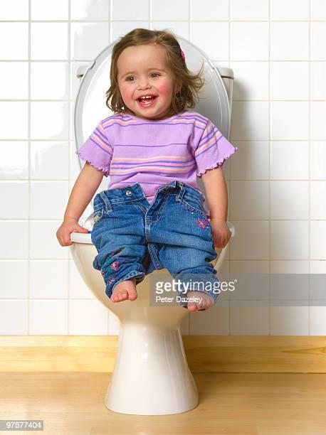 Toddler sitting on toilet training seat
