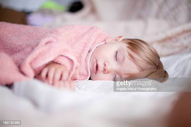 Toddler sleeping covered with pink blanket.
