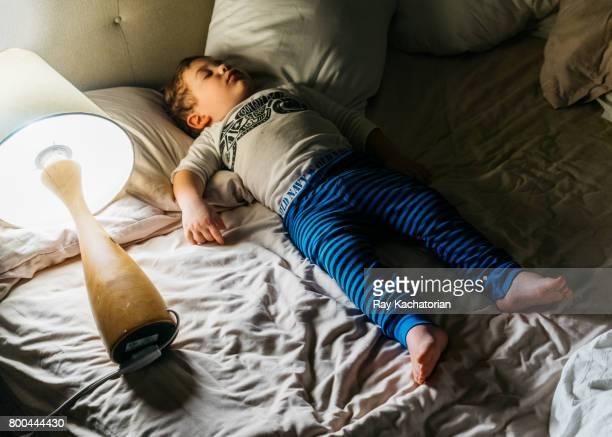 Toddler sleeping next to lamp