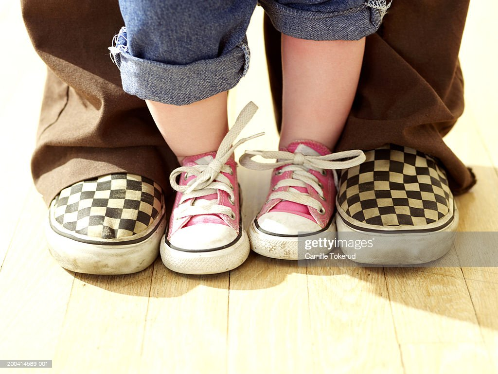 Toddler (15-18 months) standing between adult's feet, low section : Stock Photo