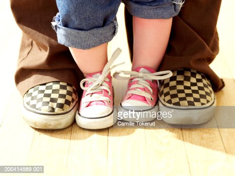 Toddler (15-18 months) standing between adult's feet, low section : Foto stock