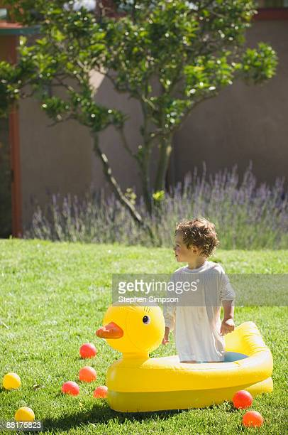 Toddler standing in inflatable duck pool