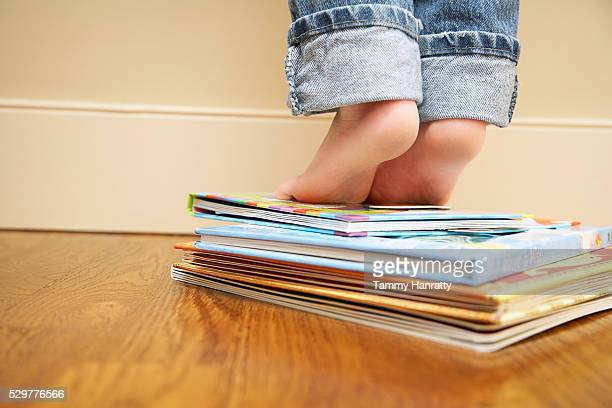 Toddler standing on books