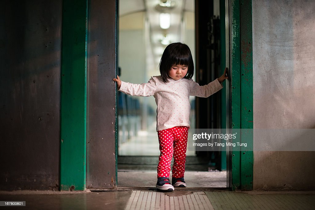 Toddler stepping out of a door under warm sunlight : Stock Photo