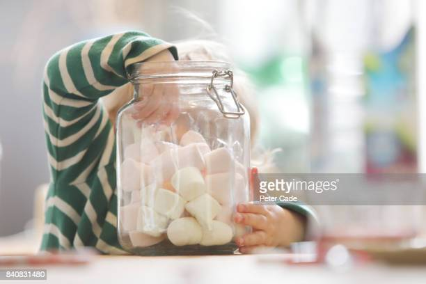 Toddler taking marshmallows out of large glass jar