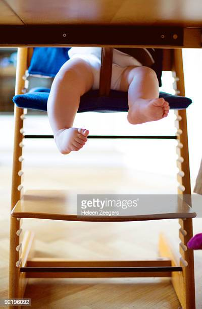 Toddler toes legs feet under table in feedingchair