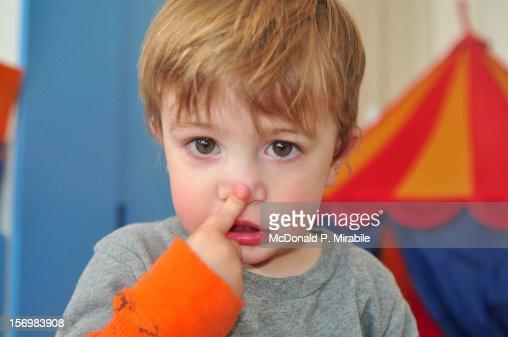 Toddler touching nose : Stock Photo