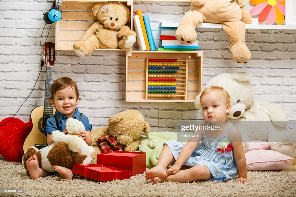 Toddler twins playing together at home : Stock Photo