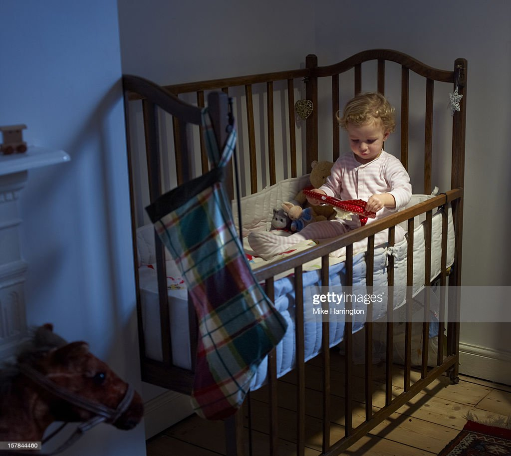 Toddler unwrapping present in cot in evening. : Stock Photo