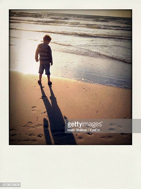 A toddler walking alone on a beach
