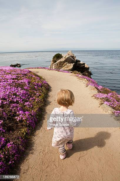 Toddler walking along path next to pink flowers