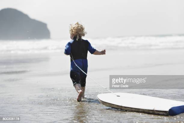 Toddler walking into sea with bodyboard