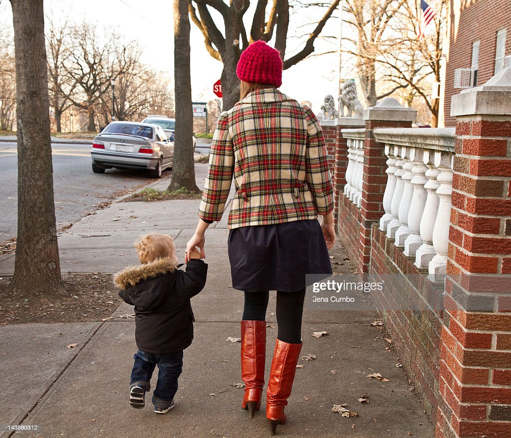 A toddler walking with his mother : Stock Photo
