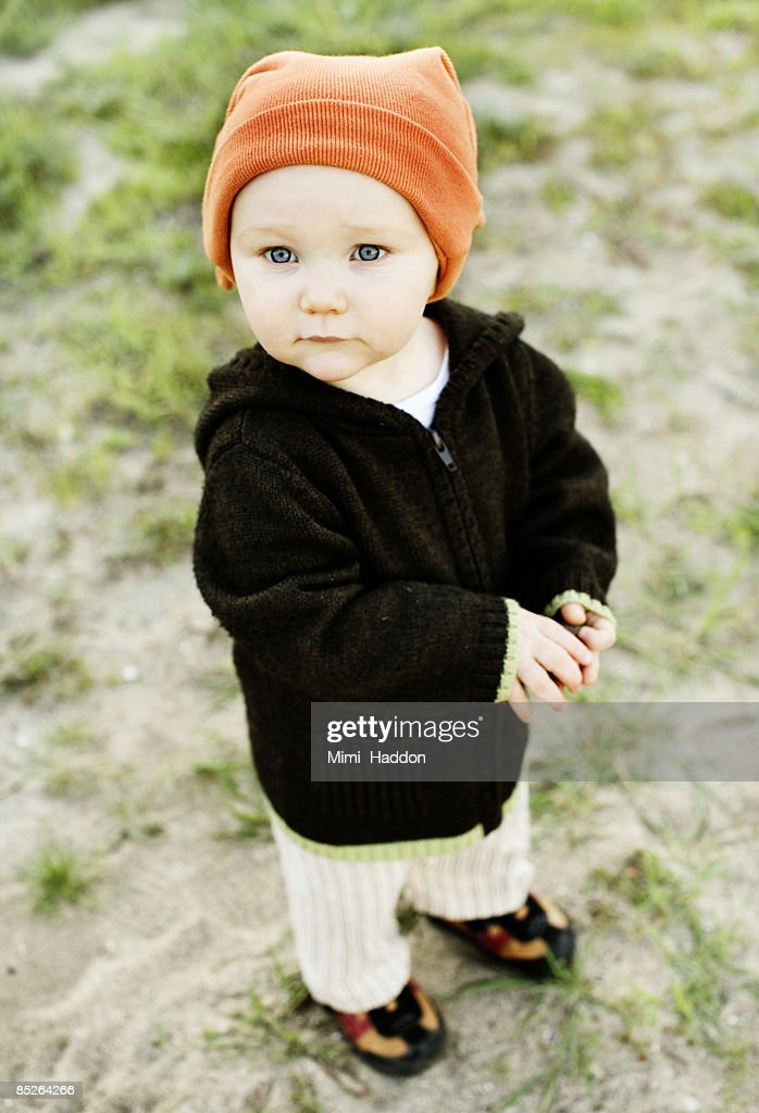 toddler wearing orange hat outside : Stock Photo