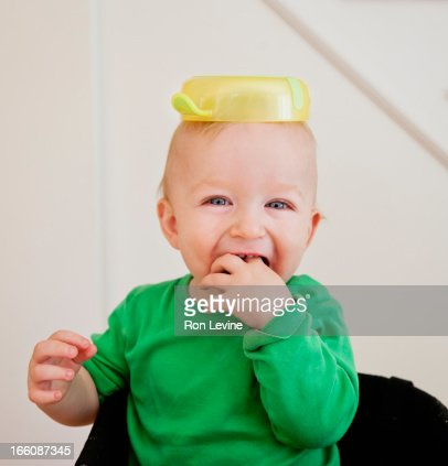 toddler with bowl upon his head, laughing : Foto de stock
