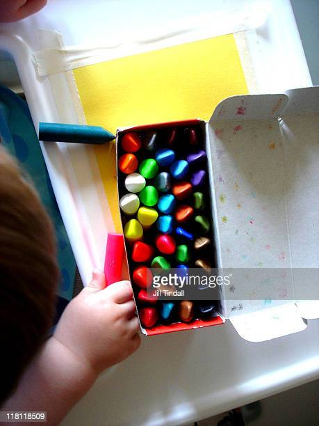 Toddler with box of colourful crayons